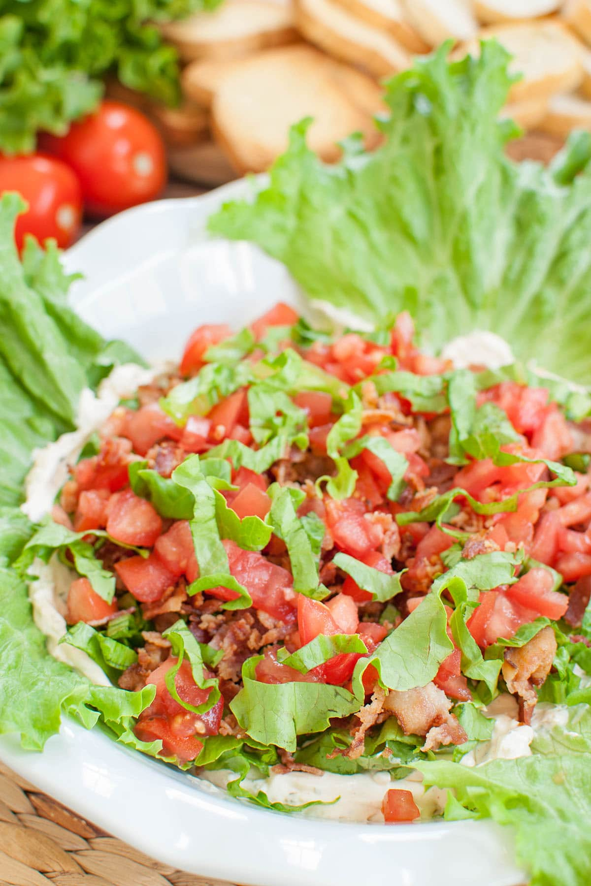 blt dip in a white dish with lettuce leaves