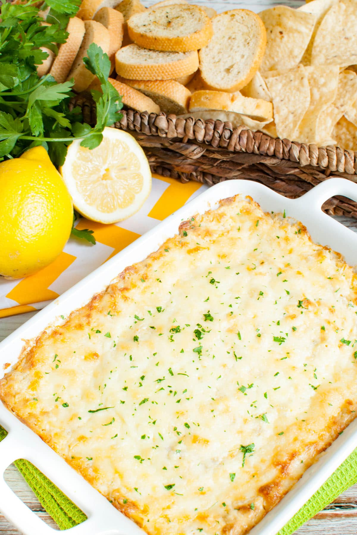 white baking dish of hot artichoke dip with a long basket of dippers