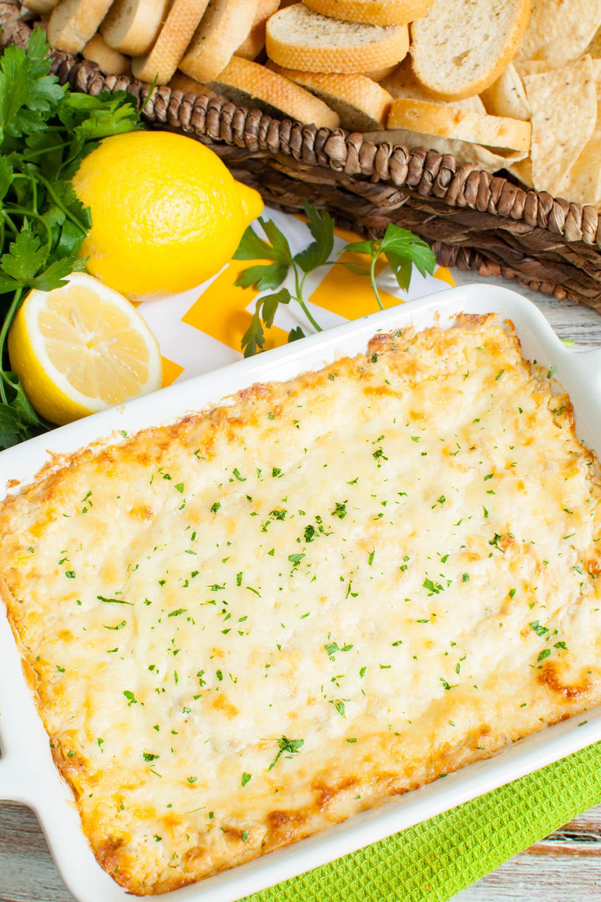 white baking dish of artichoke dip with lemons, parsley and a basket of dippers