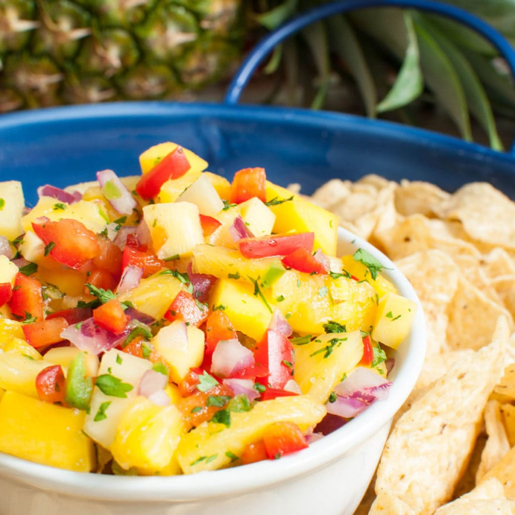 pineapple mango salsa in a white bowl on a blue platter with cips