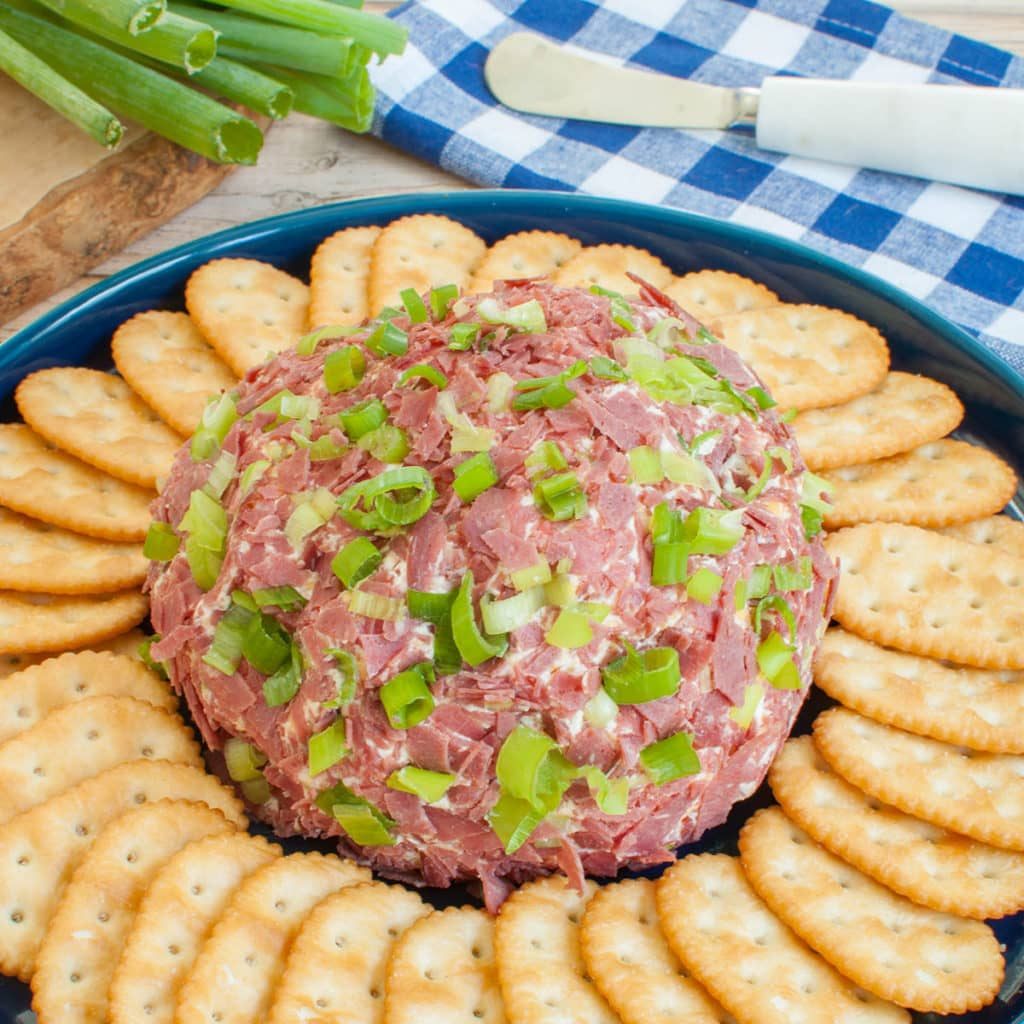 dried cheese ball on platter with crackers