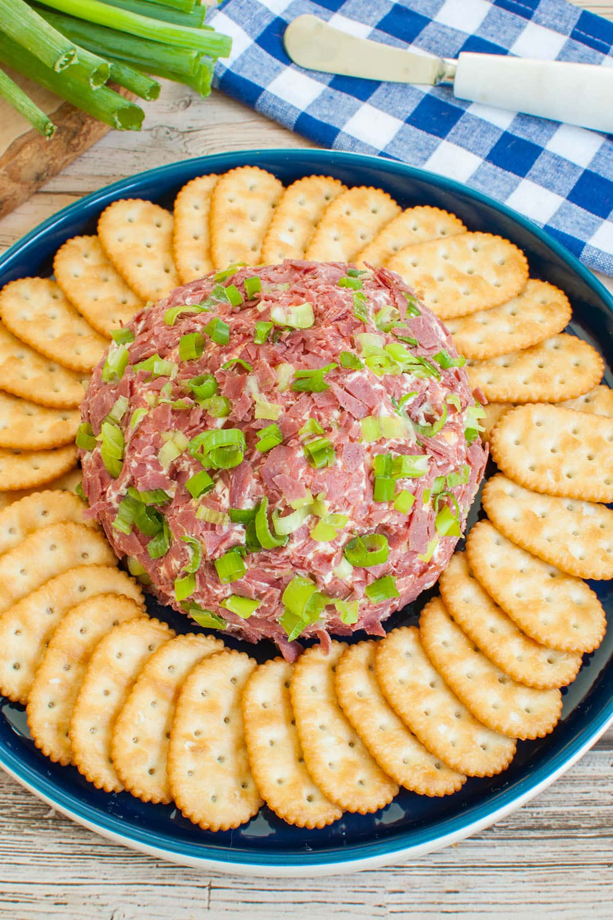 dried beef cheese ball on blue platter with crackers